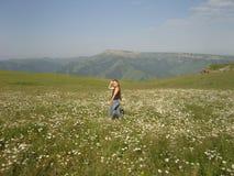 Los campos en verano de las montañas florecen a la mujer stralling fotos de archivo