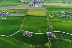 Los campos verdes claros con las granjas de un ` s del pájaro observan la visión Foto de archivo
