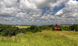 Los campos verdes con los molinoes de viento y una casa de madera estructuran considerado mientras tanto fotografía de archivo