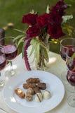 Los candys y los vidrios de las trufas de chocolate con el vino rojo en blanco cortejan Imágenes de archivo libres de regalías
