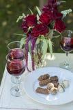 Los candys y los vidrios de las trufas de chocolate con el vino rojo en blanco cortejan Fotos de archivo libres de regalías
