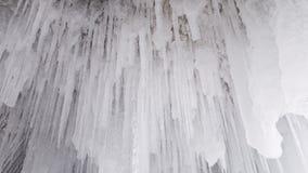 Los carámbanos blancos como la nieve largos cuelgan del techo de una cueva de hielo cerca de la isla de Olkhon en Siberia en Rusi imagen de archivo