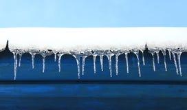 Los carámbanos cuelgan abajo de debajo el tejado de la casa Modelo congelado del invierno Fotos de archivo libres de regalías