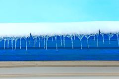 Los carámbanos cuelgan abajo de debajo el tejado de la casa Modelo congelado del invierno Foto de archivo
