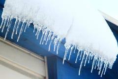 Los carámbanos cuelgan abajo de debajo el tejado de la casa Paisaje del invierno Imágenes de archivo libres de regalías