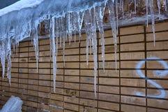 Los carámbanos cuelgan del tejado de la pared vieja, del último invierno o de la primavera temprana fotografía de archivo libre de regalías