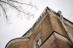 Los carámbanos cuelgan peligroso en el tejado de una casa de dos pisos fotografía de archivo libre de regalías