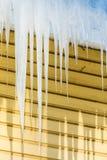 Los carámbanos que cuelgan del borde del tejado imagenes de archivo