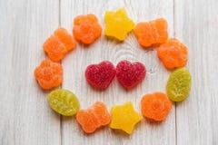 Los caramelos coloridos y el corazón rojo forman los caramelos de la jalea De madera blanco Imagenes de archivo