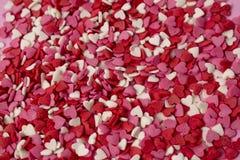 Los caramelos en forma de corazón muy pequeños se dispersan a través del fondo Muchos pequeños corazones brillantes en bulto imagen de archivo