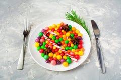 Los caramelos en la placa con platos y cubiertos les gusta el concepto malsano de la comida, chri Foto de archivo