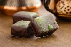 Los caramelos hechos a mano adornados con el chocolate verde salpican en la madera Imagen de archivo libre de regalías