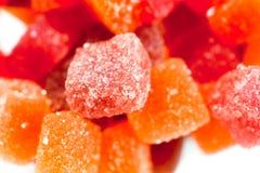 Los caramelos rojos, amarillos y anaranjados de la jalea tiraron cerca para arriba en un fondo blanco imagen de archivo