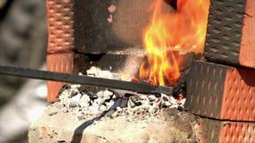 Los carbones de las mezclas del hombre en un fuego para forjar lanzaron Carbones en la chimenea improvisada almacen de video