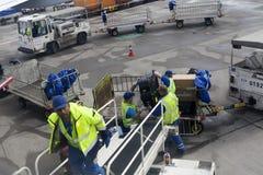Los cargadores en el aeropuerto descargan equipaje de los aviones Foto de archivo libre de regalías