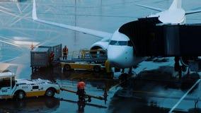 Los cargadores trajeron el equipaje a la banda transportadora del avión, preparándose para cargar las maletas a bordo imagen de archivo