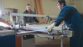 Los carpinteros de los trabajadores están cortando el detalle de madera en la sierra eléctrica en la fábrica de los muebles imágenes de archivo libres de regalías