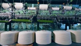 Los carretes de costura están desenrollando mecánicamente en una fábrica de la materia textil almacen de metraje de vídeo