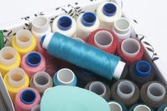Los carretes de los hilos de diversos colores se doblan en una caja Hilos de diversos colores Accesorios para coser y la costura Fotos de archivo