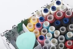Los carretes de los hilos de diversos colores se doblan en una caja Hilos de diversos colores Accesorios para coser y la costura Fotografía de archivo