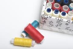 Los carretes de los hilos de diversos colores se doblan en una caja Algunas bobinas mienten de lado a lado en la tabla Accesorios Fotografía de archivo libre de regalías