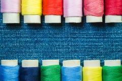 Los carretes del hilo de coser coloreado arreglaron en dos filas en el dril de algodón con el espacio de la copia fotos de archivo libres de regalías
