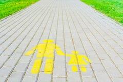 Los carriles peatonales firman en fondo del campo de la calzada y de hierba verde Foto de archivo libre de regalías