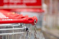 Los carros de la compra de la cadena de supermercados alemana, Rewe se unen en fila en aparcamiento Imagen de archivo libre de regalías