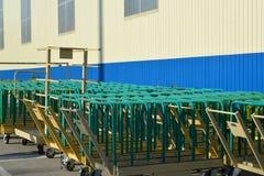 Los carros del cargo se colocan cerca del edificio de la instalación moderna Foto de archivo