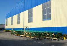 Los carros del cargo se colocan cerca del edificio de la instalación moderna Imagen de archivo