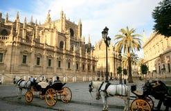 Los carros traídos por caballo acercan a la catedral, Sevilla Imágenes de archivo libres de regalías