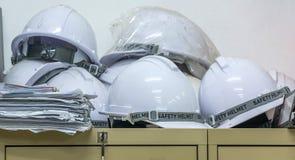 Los cascos de seguridad del trabajador en constructor encendido rematan el gabinete Imagen de archivo libre de regalías