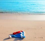 Los casquillos del Año Nuevo en la arena en el mar. Aún-vida en un día soleado Imagen de archivo libre de regalías