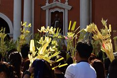 Los católicos que agitan hojas de palma del coco en la celebración de Ramos Domingo antes de Pascua, fondo de la torre de iglesia foto de archivo libre de regalías