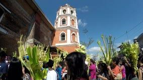 Los católicos que agitan hojas de palma del coco en la celebración de Ramos Domingo antes de Pascua, fondo de la torre de iglesia almacen de metraje de vídeo