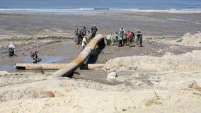 Los cazadores furtivos en la forma de goma conducen sus actividades en fango en la costa metrajes