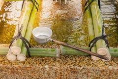 Los cazos japoneses del agua para el cuerpo y el corazón de la pureza antes del paseo al templo japonés que es creen de la religi imagenes de archivo