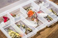 Los cebos de cuchara, engañan, las moscas, trastos en la caja para coger o pescar un pescado depredador en fondo de madera de la  Foto de archivo libre de regalías