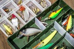 Los cebos de cuchara, engañan, las moscas, trastos en la caja para coger o pescar un pescado depredador en fondo de madera de la  Imagen de archivo