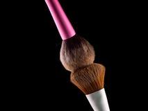 Los cepillos cosméticos del maquillaje en sombra negra del polvo del chapoteo de la explosión del flash del fondo se ruborizan Foto de archivo