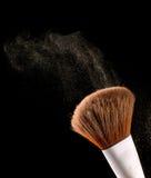 Los cepillos cosméticos del maquillaje en sombra negra del polvo del chapoteo de la explosión del flash del fondo se ruborizan Imagen de archivo libre de regalías