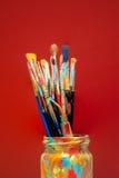 Los cepillos de pintura de los artes en estudio sacuden con el fondo rojo Foto de archivo