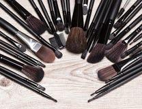 Los cepillos del maquillaje arreglaron en semicírculo en superficie de madera lamentable Imágenes de archivo libres de regalías