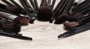 Los cepillos del maquillaje arreglaron en semicírculo en superficie de madera lamentable Foto de archivo