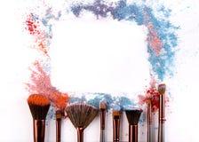Los cepillos del maquillaje con se ruborizan o sombreador de ojos de tonos rosados, azules y coralinos asperjado en el fondo blan Imagenes de archivo