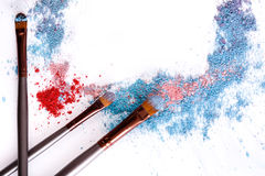 Los cepillos del maquillaje con se ruborizan o sombreador de ojos de tonos rosados, azules y coralinos asperjado en el fondo blan Foto de archivo