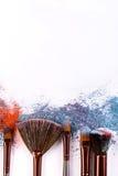 Los cepillos del maquillaje con se ruborizan o sombreador de ojos de tonos rosados, azules y coralinos asperjado en el fondo blan Fotos de archivo libres de regalías