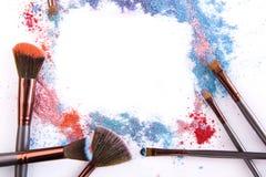 Los cepillos del maquillaje con se ruborizan o sombreador de ojos de tonos rosados, azules y coralinos asperjado en el fondo blan Fotografía de archivo libre de regalías