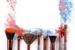 Los cepillos del maquillaje con se ruborizan o sombreador de ojos de tonos rosados, azules y coralinos asperjado en el fondo blan Imagen de archivo libre de regalías