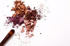 Los cepillos del maquillaje con se ruborizan o sombreador de ojos de tonos rosados, rojos y coralinos asperjado en el fondo blanc Foto de archivo